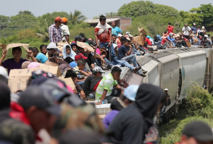 JUCHITAN, MEXICO - AUGUST 06: Central American immigrants ride north on top of a freight train on August 6, 2013 near Juchitan, Mexico. Thousands of Central American migrants ride the trains, known as 'la bestia', or the beast, during their long and perilous journey through Mexico to reach the U.S. border. Some of the immigrants are robbed and assaulted by gangs who control the train tops, while others fall asleep and tumble down, losing limbs or perishing under the wheels of the trains. Only a fraction of the immigrants who start the journey in Central America will traverse Mexico completely unscathed - and all this before illegally entering the United States and facing the considerable U.S. border security apparatus designed to track, detain and deport them. (Photo by John Moore/Getty Images)