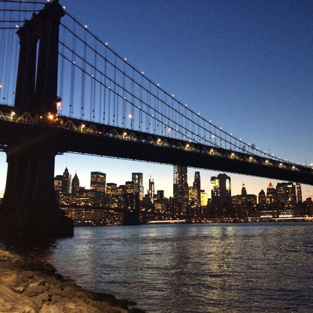Brooklyn Bridge and the East River with Manhattan skyline at dusk, view from Brooklyn