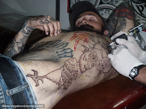 Wade receiving a tattoo of a cockfight in Mexico