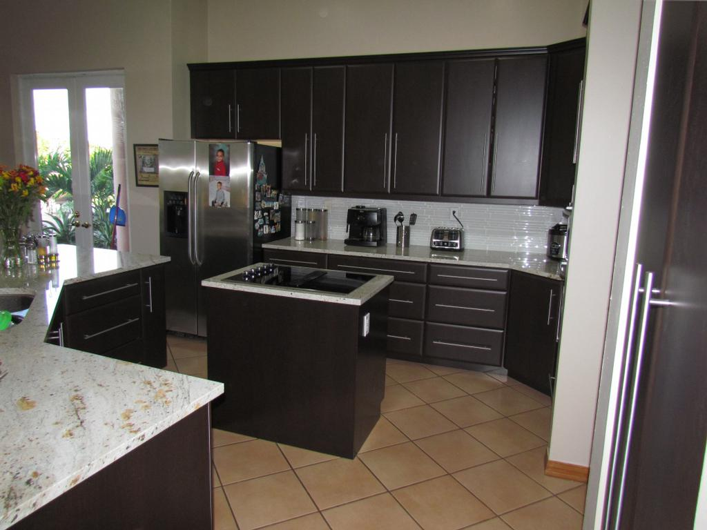 Black kitchen cabinet refacing with silver handle plus frige near the door