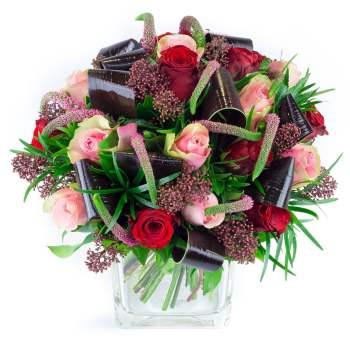 Bouquet hivernal composé de roses rouges, roses roses, véroniques roses et travail de feuillage.