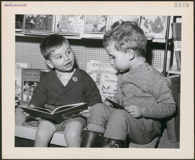 Two young boys, seated with books, in the children's department of a Toronto public library, Toronto, Ontario