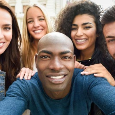 Multiracial group of friends taking selfie in a urban street with a black man in foreground. Three young women and two men wearing casual clothes.