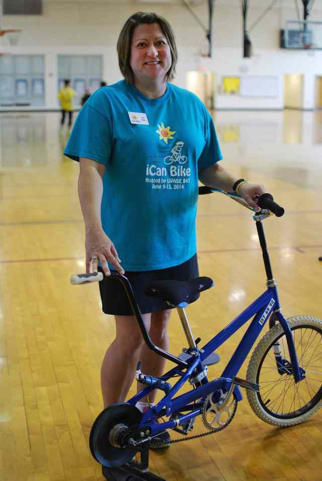 Founder and Executive Director Lisa Ruby stands with one of the bikes used for programming.