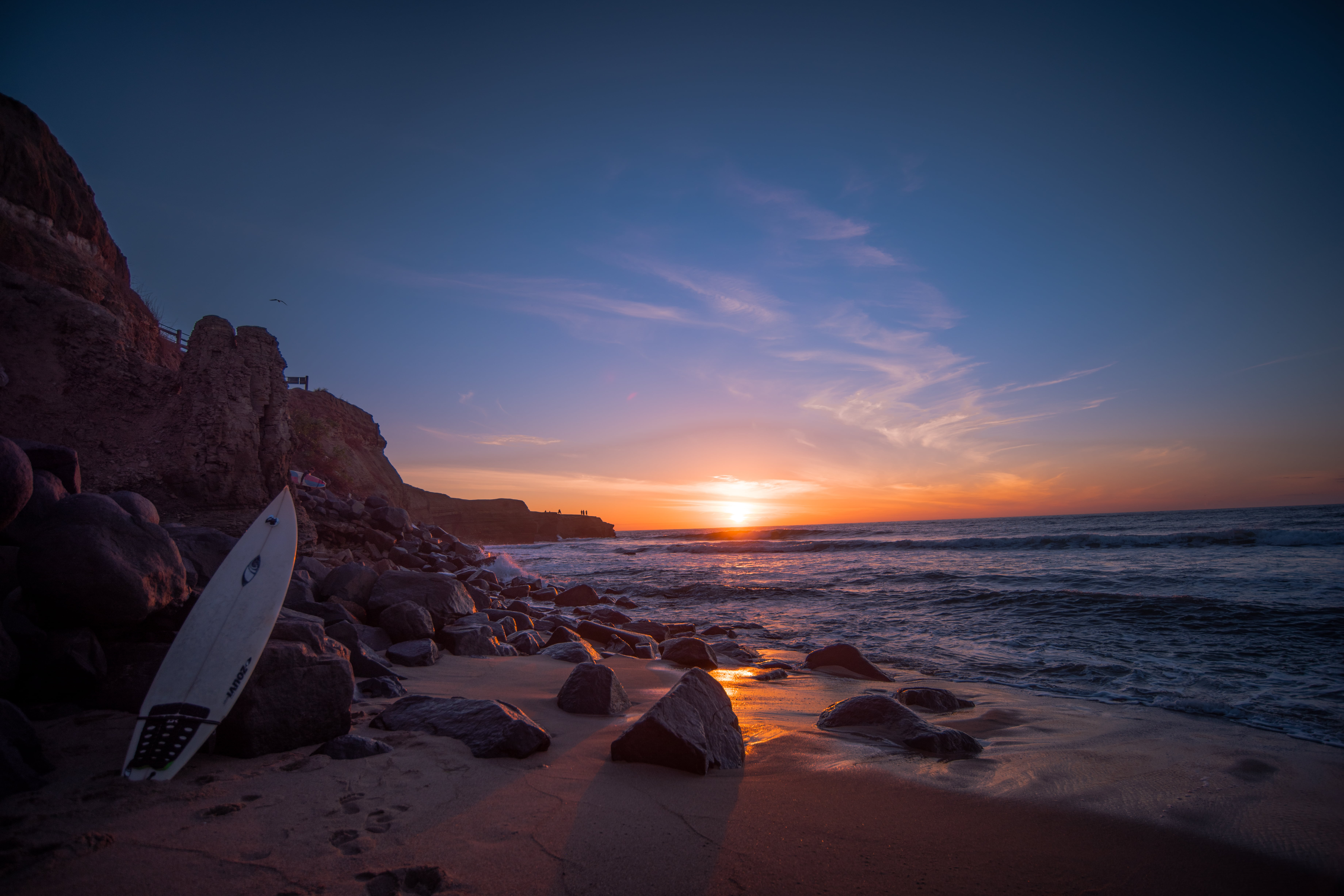 San Diego Wallpaper Hd White Surfboard Leaning On Rock Near Water At Sunset Hd