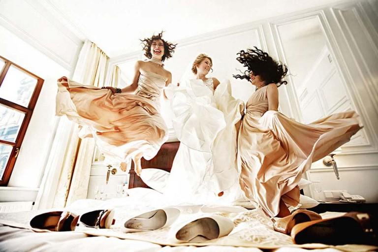 bride and bridesmaid jumping on bed having fun