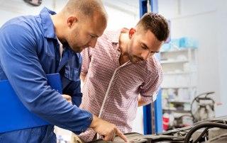 Werkstattmeister zeigt dem Kunden die defekte Stelle
