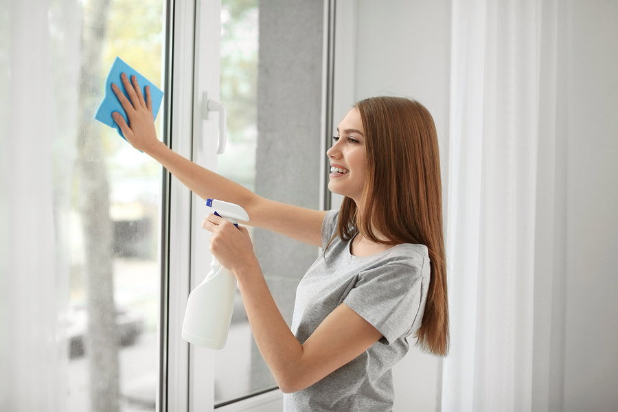Woman cleaning vinyl windows at home