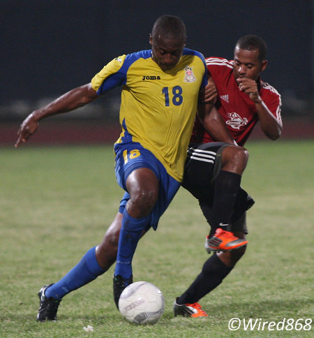 Photo: Defence Force midfielder Sean  Narcis (left) holds off a tackle for Central FC opponent Hayden Tinto. (Courtesy Wired868)