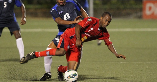 Photo: Caledonia AIA captain Stephan David is knocked over by Police midfielder Kenaz Williams in a previous fixture. (Courtesy TT Pro League)