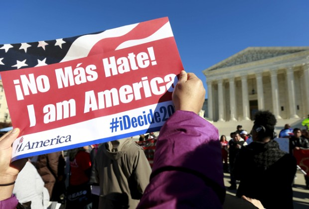A protester holds a sign as immigrants and community leaders rally in front of the U.S. Supreme Court to mark the one-year anniversary of President Barack Obama's executive orders on immigration in Washington, in this file photo taken Nov. 20, 2015. — PHOTO: REUTERS/Kevin Lamarque/Files