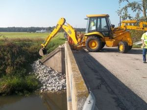 Starke County Highway Department workers add rip rap to bridges.