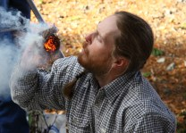 Instructor-Jason-Patterson-blows-bow-drill-coal-into-flame