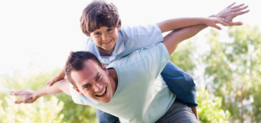 Man and young boy outdoors playing airplane smiling