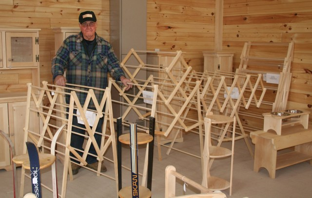 Glen Tompkins displays his wares in the showroom of his workshop. Glen's best-selling product is a line of folding clothes drying racks he manufactures for a chain of Maine department stores. He also builds a number of other product lines including picnic tables, Adirondack chairs, and items shown here..