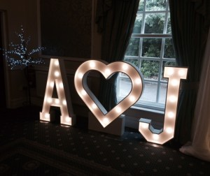 A heart J light up initials decorating a wedding party