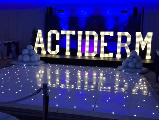 ACTIDERM Illuminated letters on stage at a Christmas party celebration