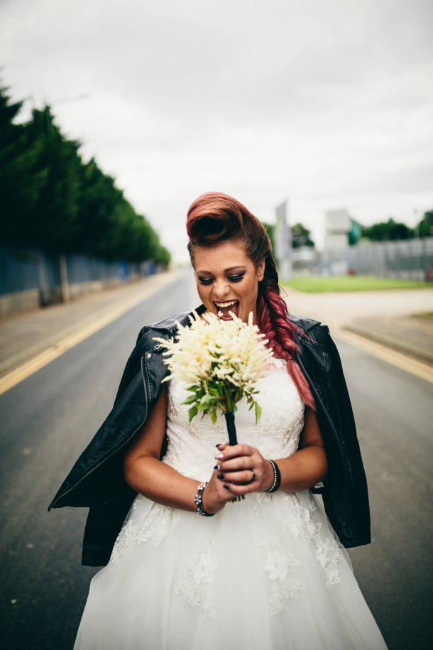 Bride walking down the road rocking her bridal bouquet and leather biker jacket
