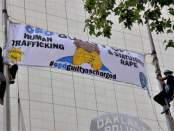 Activists scale OPD flag poles for banner drop, June 17.
