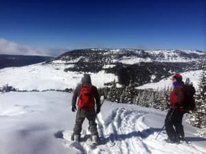 Anthony Tarver and Mark Weitz reach the top of Antelope Butte and prepare to ski and snowboard back down. Tarver learned to ski and snowboard at the hill. Weitz' children also learned to ski at the area which closed in 2004. (Kelsey Dayton/WyoFile)