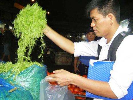 Cán bộ Chi cục BVTV TP.HCM đang lấy mẫu rau muống bào kinh doanh ở chợ đầu mối Hóc Môn để xét nghiệm.