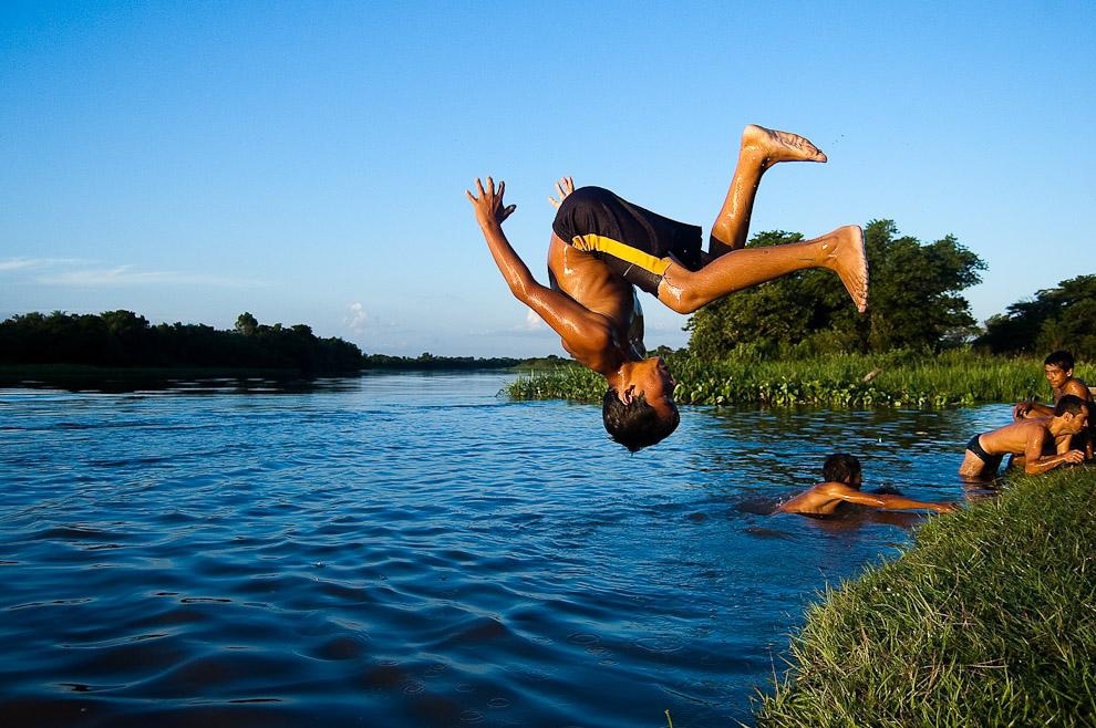 Un muchacho se divierte saltando al Río Jejuí con sus amigos en una tarde del viernes santo, luego de una jornada de pesca que duró casi todo ese día. (San Pedro, Paraguay - Elton Núñez)
