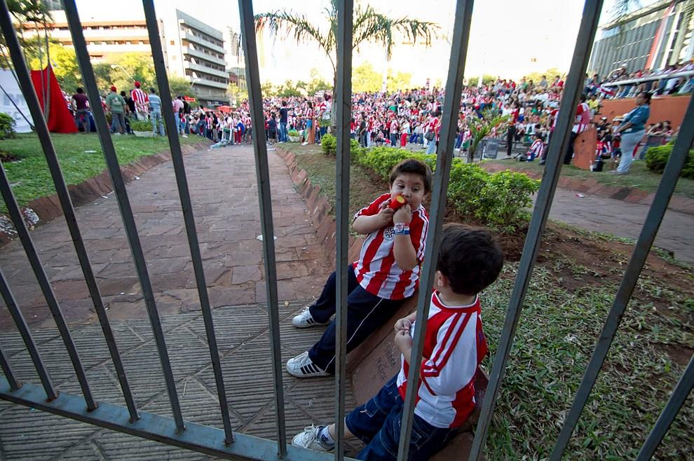 Dos niños pequeños juegan mientras el público asiste el encuentro. (Tetsu Espósito, Asunción, Paraguay)