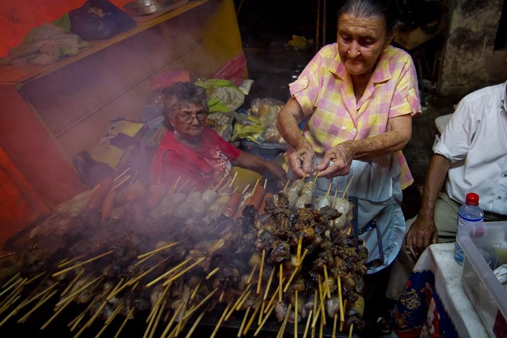 Esta abuelita cocinaba con mucha habilidad, asaditos de carne vacuna y de cerdo, butifarra y chorizos en uno de los tantos puestos de comida habilitados en la ciudad. (Tetsu Espósito - Caacupé - Paraguay