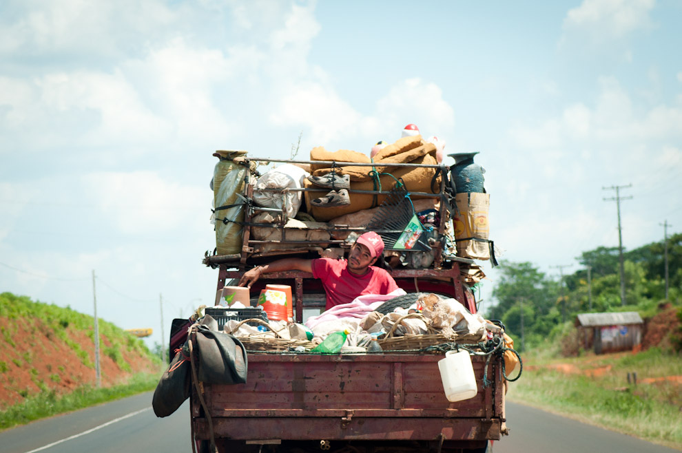 Un muchacho viaja en la carrocería de una camioneta entre bultos, paquetes y artesanías envueltas, en el trayecto de la ruta 3 Santani - 25 de Diciembre del Departamento de San Pedro. (Elton Núñez - Santaní, Paraguay)