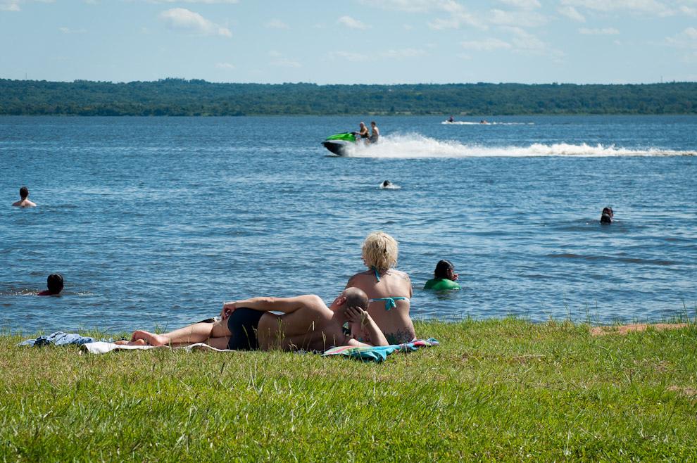 En el verano paraguayo una pareja disfruta el sol en la playa del Lago Ypacaraí mientras otros se refrescan en el agua. El paseo en jetsky es otra habitual actividad en el lago más importante de la ciudad veraniega de San Bernardino. El lago Ypacaraí abarca aproximadamente 90 km² de superficie y sus dimensiones son 24 km de norte a sur y 5 a 6 km de este a oeste. Su profundidad media es de 3 metros. El paisaje que conforma el lago es muy bello, pues está rodeado por cerros con espesa vegetación y por tres pueblos que se extienden en las elevaciones circundantes.(Elton Núñez - Ypacaraí - Paraguay)
