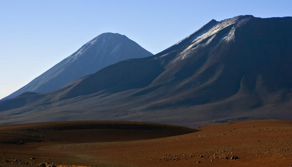 El desierto más árido del planeta Tierra nos muestra su aspecto silencioso, frío y a la vez, majestuoso e imponente. Vemos dos volcanes convenientemente dormidos. Atacama, Chile. (Guillermo Morales)