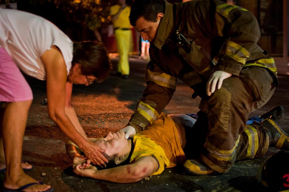 Un bombero voluntario mantiene quieta la cabeza de una víctima de accidente de motocicleta mientras llega la ayuda. Sucedió en un violento accidente registrado  en las calles 4ta y O'leary. En dicho accidente dos personas salieron gravemente heridas, se necesitó el apoyo de una segunda ambulancia de la 5ta. compañía de Lambaré para el traslado de los heridos al hospital de emergencias médicas. (Elton Núñez).