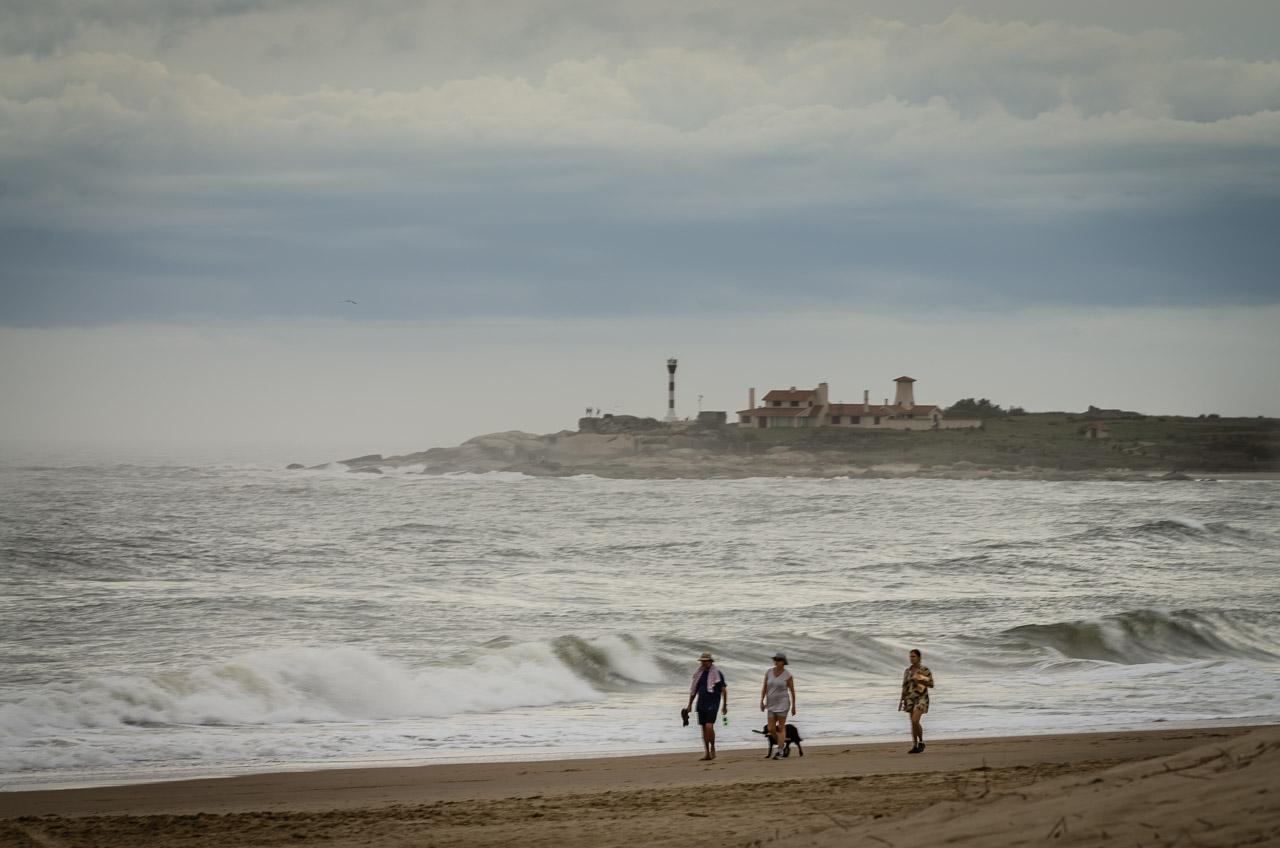 Turistas aprovechan la tarde para caminar por la Playa de la Viuda, en el fondo se puede apreciar una punta en la cual fue construida el Faro Punta Palmar. (Elton Núñez).