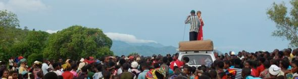 A visiting DTS student stands atop our car with two thousand people gathered to hear the gospel after a football match.