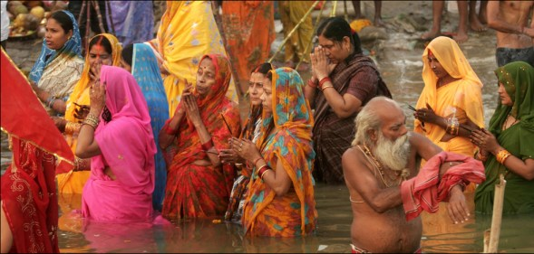 Hindu devotees offer prayers on the occasion of the festival of Chhat, dedicated to the worship of the Sun God, as they stand in the River Ganges in Allahabad, India