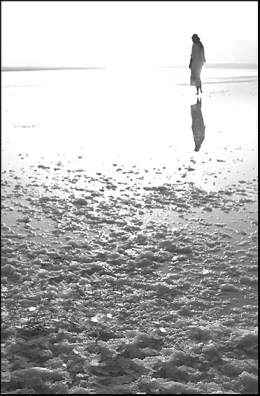 Lonely woman walking alone on the beach