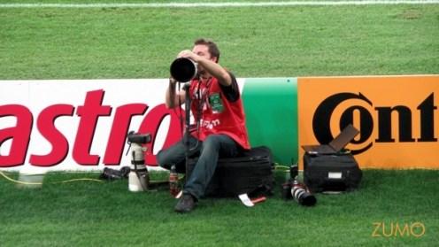 um fotógrafo com colete vermelho (diferente dos demais) fica de olho na plateia. Ele tem... 3 câmeras!