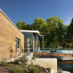 West entrance, view of rammed-earth-wall and waterfall scupper, Image Courtesy © Nick Lehoux