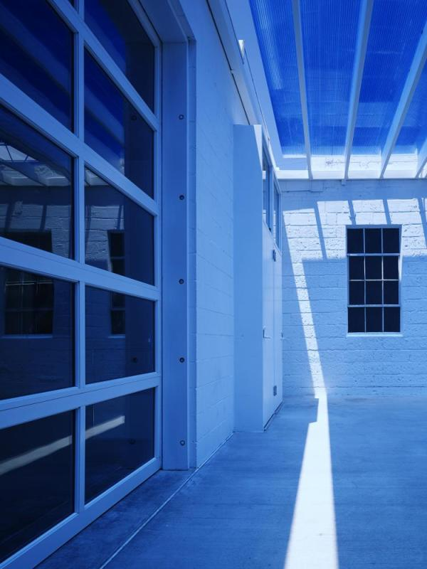 Detail under the entry canopy showing the blue polycarbonate and the existing steel windows. The sun creates magical changes throughout the day.  The space remains a deep blue during daylight hours, Image Courtesy © Elliott + Associates Architects