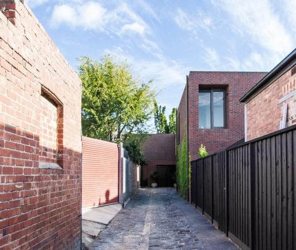 A small cluster of buildings create three separate residences along a laneway, Image Courtesy © B.E ARCHITECTURE