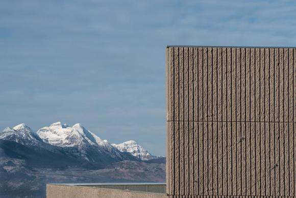 view of the near mountain juxtaposed to the peculiar mass and texture of the building, Image Courtesy © Alessandro Ruzzier