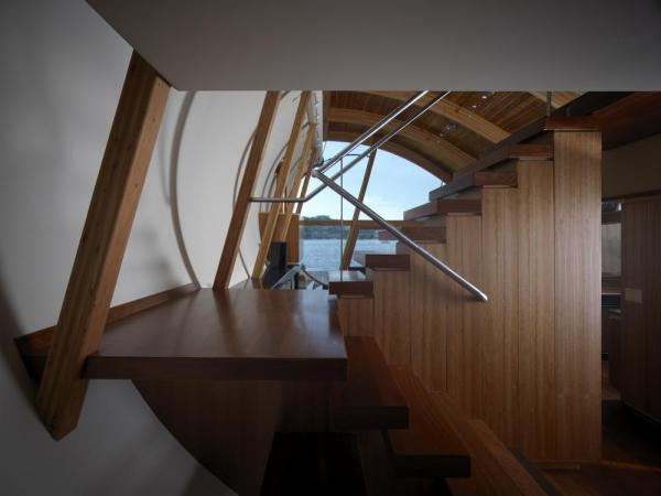 A Stair detail displaying the Brazilian Cherry wood used throughout the  residence as flooring. The staircase separates the entry from the main living space, Image Courtesy © Robert Harvey Oshatz, Architect
