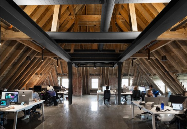 The soaring double height spaces, with their immense timber beams, create an awe-inspiring work environment, Image Courtesy © Adrien Williams