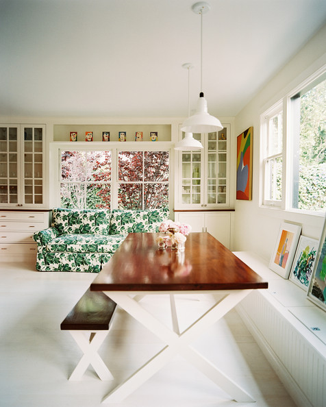 Dining table with bench a floral print green couch and an x base
