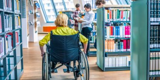 Student sitting on a wheelchair in library with schoolmates