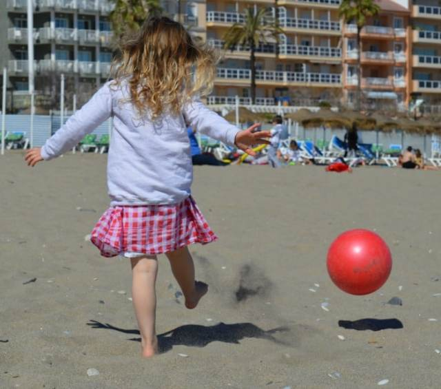 child playing ball on the beach