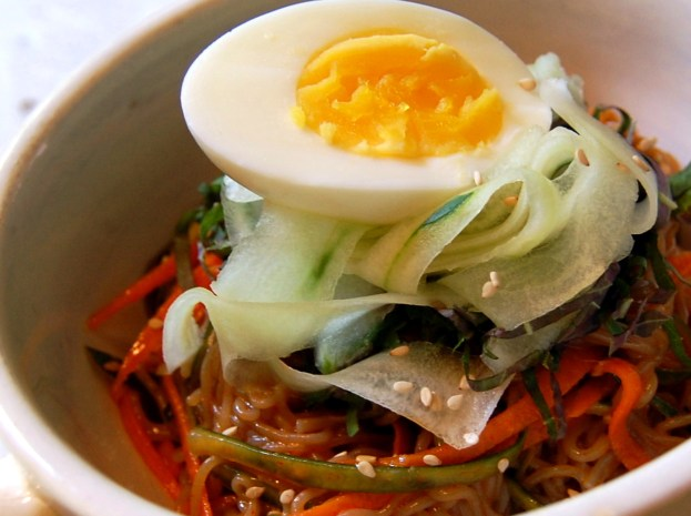 Naengmyeon with julienned carrot, perilla leaves, shaved cucumber, toasted sesame seeds and 1/2 boiled egg