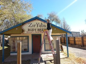 Kevin hangs our new sign at shop in Silver City New mexico