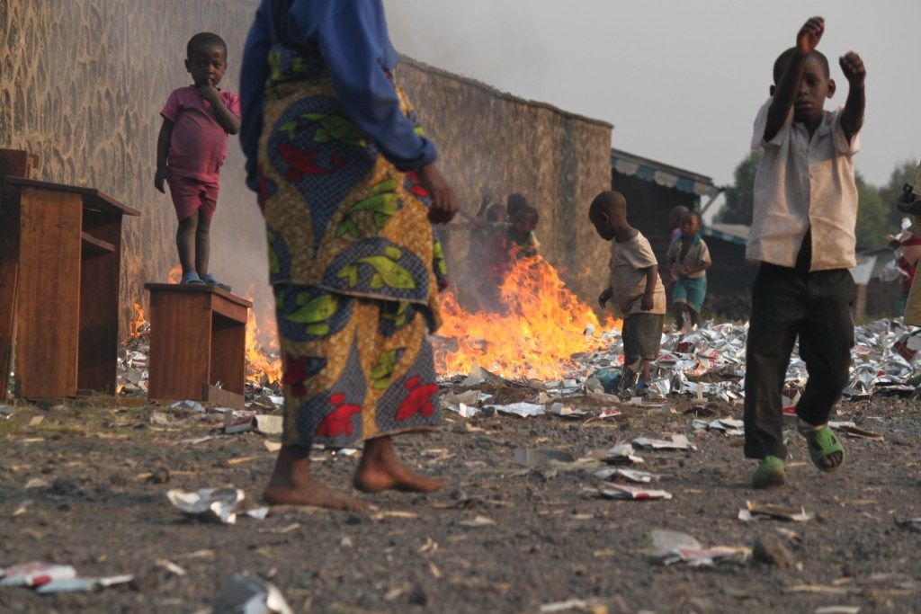 The local community burn their waste in a corner of Kibati camp. School desks have been taken out of the nearby school to make room for people now seeking shelter there.