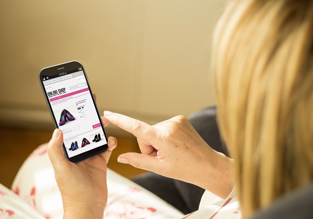 modern comerce or lifestyle concept:  woman with 3g generated smartphone with online shop interface on the screen. All screen graphics made up.